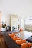Elegant living room with corner sofa, fireplace and panoramic view of landscape