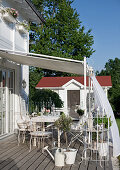 Delicate, white metal chairs on wooden terrace of country house