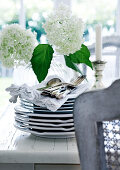 Silver cutlery on stack of plates in front of vase of white flowers