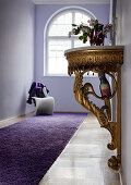 Rococo console table in lilac period hallway; white Panton chair below arched window in background