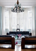 Black 60s designer sofas and wrought iron chandelier in front of bay window in period living room