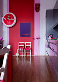 Objet d'art and beer advert in modern living-dining room against walls painted in vibrant pink and red