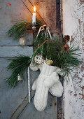 Advent arrangement of mittens, branches, baubles and pine cones on door