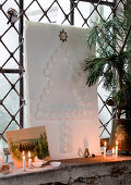 Christmas tree of white paper sweet cases on sheet of paper