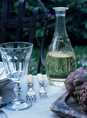 Carafe of white wine and rustic wine glass on set table in garden