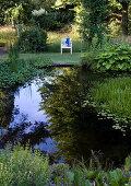 Stuhl steht mit Blick auf den Teich im sommerlichen Garten