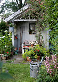 Idyllisches Gartenhaus mit Sitzplatz im Sommergarten