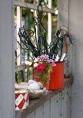 Rankhilfen, Blumen und Deko im Fenster des Gartenhauses