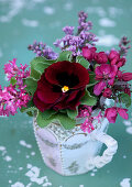 China jug of spring flowers in shades of red