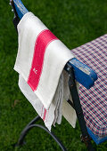 Garden chair with cushion and tea towels hanging over back