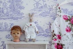 Doll's head and rabbit soft toy on shelf against Toile de Jouy wallpaper
