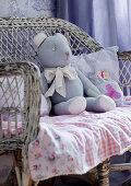 Teddy bear on gingham blanket on old wicker chair