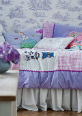 Patchwork quilt on bed against wall with Toile de Jouy wallpaper in child's bedroom