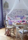 Pastries on table and rustic children's chairs in front of canopied bed in child's bedroom