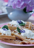 Waffles with cream and candied flowers on a pink plate