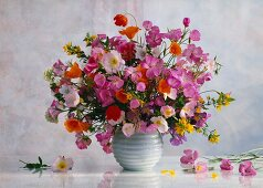 Colourful spring bouquet in spherical vase against light, clouded wall