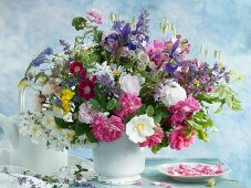 Colourful bouquet in white vase next to teapot