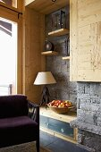 Corner of rustic, modern room with grey stone wall and purple armchair