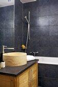 Modern bathroom with stone basin on washstand and dark grey wall tiles