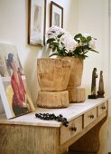 Rustic wooden containers with flowers on console table with drawers