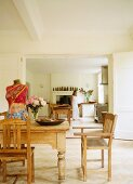 Rustic dining area with objets d'art on table and view of kitchen through open double doors