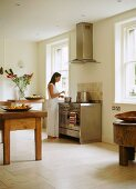 Woman seasoning food in plain kitchen with rustic table and designer cooker