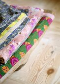 Patterned blankets on wooden floorboards