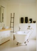 Vintage bathtub in centre of bathroom and group of black vases on shelf