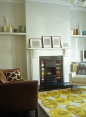 Rug with abstract floral pattern and brown leather couch in front of open fireplace