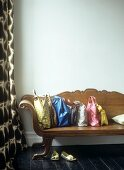 Baroque, wooden bench with collection of colourful bags on dark wooden floorboards