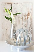 Sphere made of metal strips on metal dish and white lily in metal vase in front of vintage-style wooden board