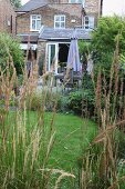 View through grasses of dining area on terrace of country house