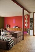 Retro living space with brown sofa and sideboard against red-painted wall