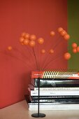 70s-style ornament with metal base and spray of spheres next to stack of books against red-painted wall