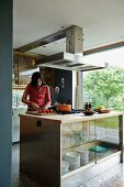 Teenager preparing food on kitchen island in open-plan kitchen