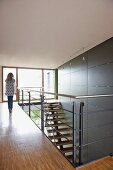 Teenager walking along gallery and staircase against wall with large grey tile panels