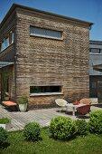 Contemporary house with wooden facade and sunny terrace on edge of garden