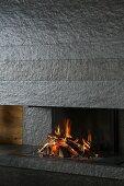 Blazing fire in open fireplace clad in dark grey stone slabs