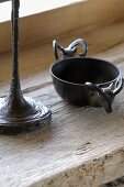 Small metal bowl decorated with ibex heads next to base of table lamp on vintage wood surface