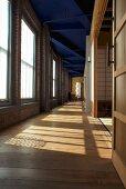 Industriehalle mit grosszügigem Gang und abgetrennten Räumen mit schiebbaren Wänden in japanischem Stil