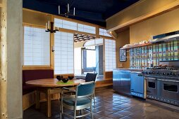 Essplatz und Edelstahl-Küchenzeile vor gelb getönter Wand
