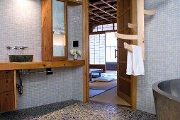 Schlichtes Bad mit Mosaikfliesen an Wand und Holzeinbauten mit offener Tür und Blick in Schlafraum in japanischem Stil