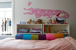 A crocodile and a heart cut out of patterned wall paper above a bed with a colourful relax pillow in a girl's bedroom