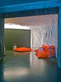 Orange Sitzsäcke auf poliertem Estrichboden in kellerartigem Wohnraum
