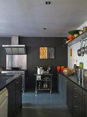 Graue Küchenzeile und Mittelblock vor Edelstahl Herd mit Dunstabzug an grau getönter Wand