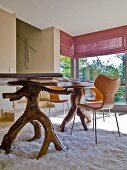 Dining table with legs made from unfinished, twisted wood on flokati rug in modern interior
