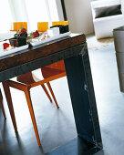 Vintage-Esstisch in Blau mit orangefarbenen Stühlen; darauf zwei Dessertteller