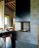 Offener Wohnraum mit zentralem, gemauerten Kamin; im Vordergrund ein Vintage- Esstisch