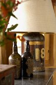Two old bottles used for decoration next to a table lamp with the base made from an antique metal container