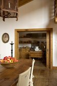 View through a sliding door into the kitchen; a dish full of apples on a rustic dining table and antique lights in a renovated country home